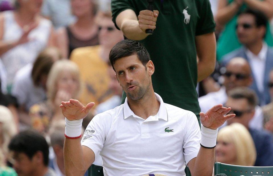Serbia's Novak Djokovic gestures to his box after