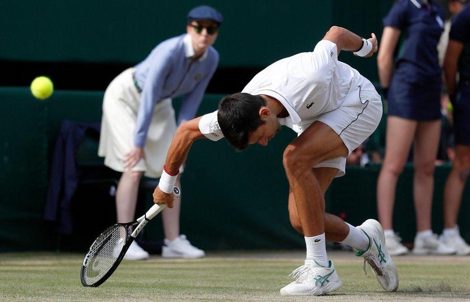 Serbia's Novak Djokovic stumbles trying to return the
