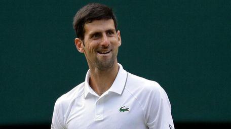 Serbia's Novak Djokovic smiles after defeating Switzerland's Roger