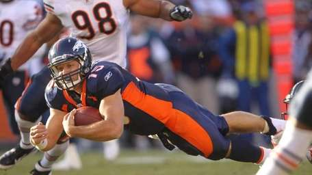 Denver Broncos quarterback Tim Tebow dives on a