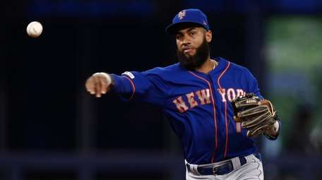 Mets shortstop Amed Rosario throws to first base