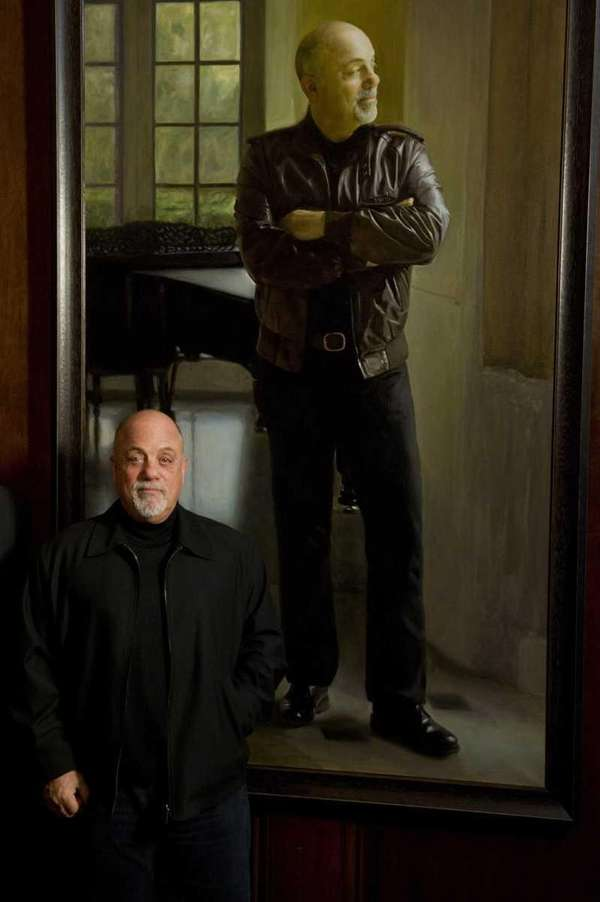 Billy Joel poses next to his portrait at