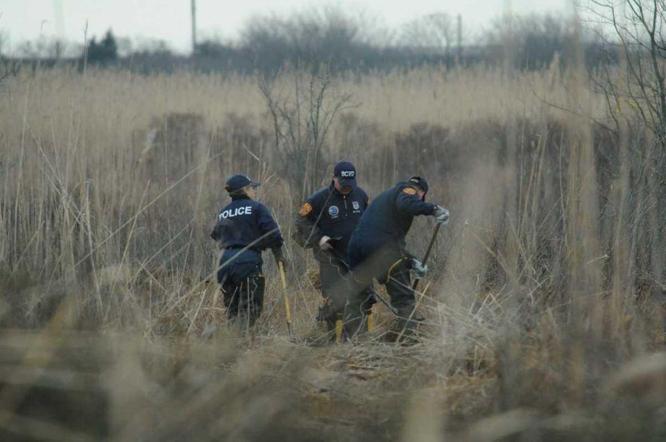 Crime scene investigators use metal detectors during a