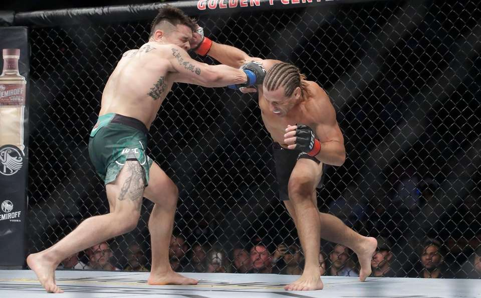 Urijah Faber, right, connects with a punch to
