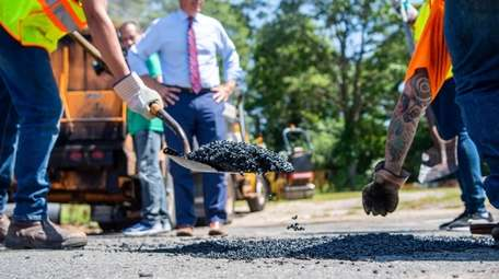 Crews fix a pothole in Commack as Suffolk