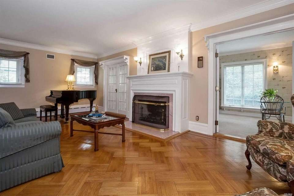 The living room features a mantled fireplace, hardwood
