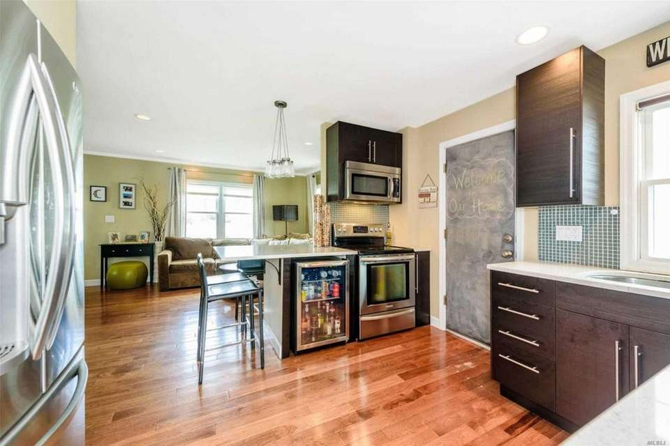 The eat-in kitchen features quartz countertops, black cabinetry