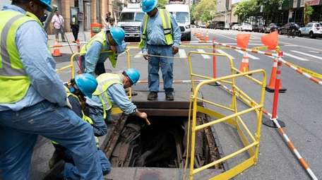 Con Edison workers on Sunday examine electrical infrastructure