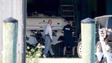 Nassau County police inspect the motor boat that