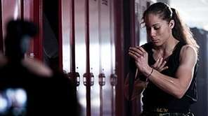 Liz Carmouche begins wrapping her hands for a