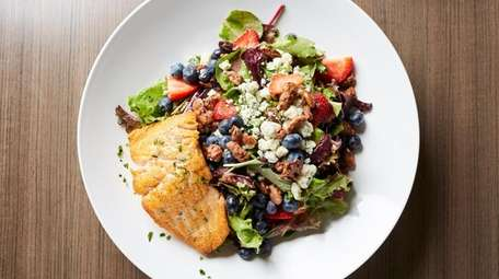 Salmon is served with a salad of greens,