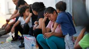 Migrants wait at an immigration center on the