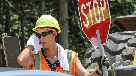 Flagger Ashley Costa of Farmingville helps control traffic