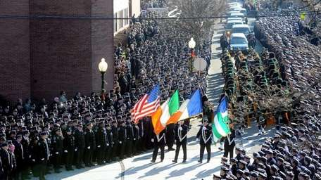 Police officers stand at attention as the funeral