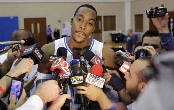 Orlando Magic's Dwight Howard, center, answers questions from