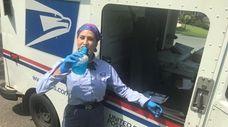 U.S. Postal Service worker Moraima Lopez pauses to