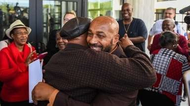 Keith Bush is embraced outside Suffolk County Court