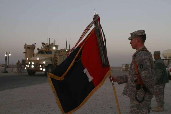 A U.S. Army soldier holds a flag as