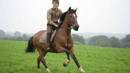 Albert Narracott (Jeremy Irvine) joyfully rides atop his