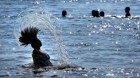 Beachgoer Blanca Menendez flings her hair through the