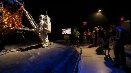 Attendees view the Grumman lunar module at the