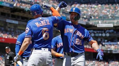 Pete Alonso, right, meets Jeff McNeil after hitting