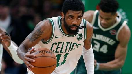 Boston Celtics' Kyrie Irving (11) brings the ball