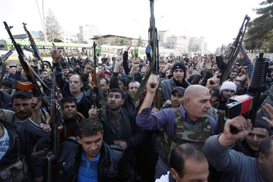 Members of Syrian security chant slogans and raise