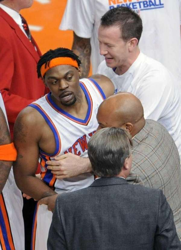 New York Knicks' Bill Walker is restrained after