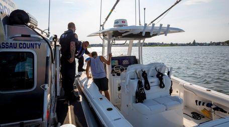 Nassau County Marine Bureau officers inspect a boat