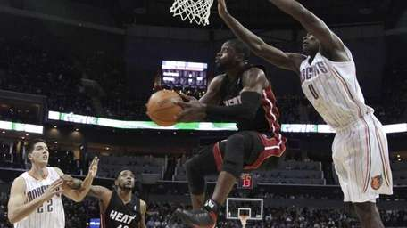 Miami Heat's Dwyane Wade, center, sails to the