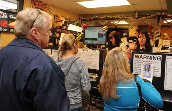 Customers lineup to purchase Mega Millions lottery tickets