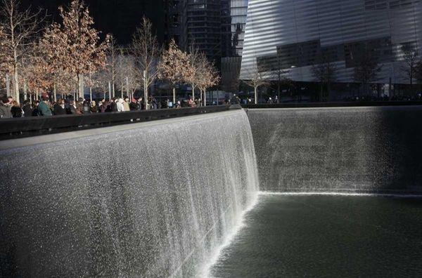Visitors walk around the National September 11 Memorial,