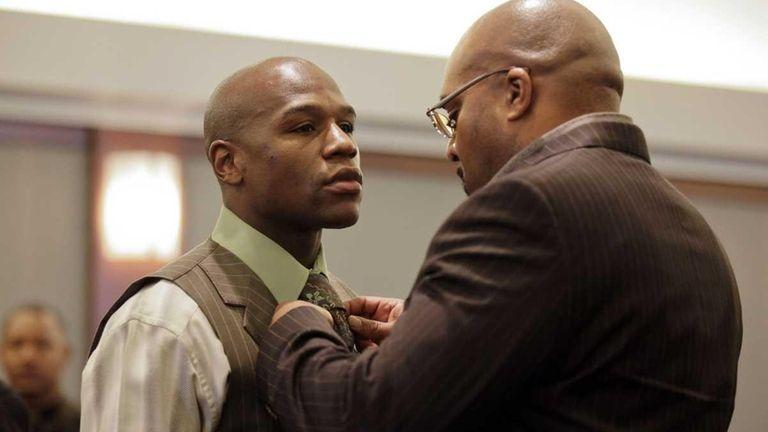Boxer Floyd Mayweather Jr., left, has his tie