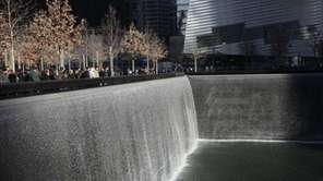 Visitors walk around the National September 11 Memorial