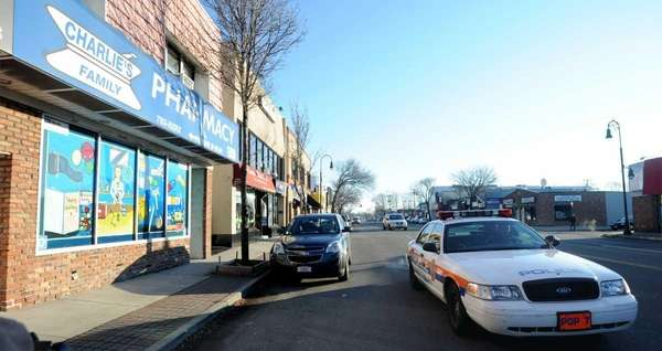 A Nassau police cruiser passes Charlie's Family Pharmacy