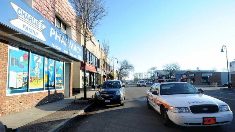 A Nassau police cruiser passes Charlie's Family Pharmacy