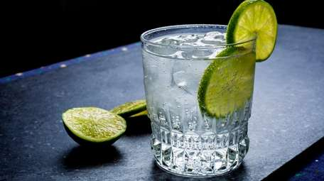 Gin and tonic garnished with a lime.