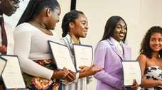 Students show off their certificates as nearly 50