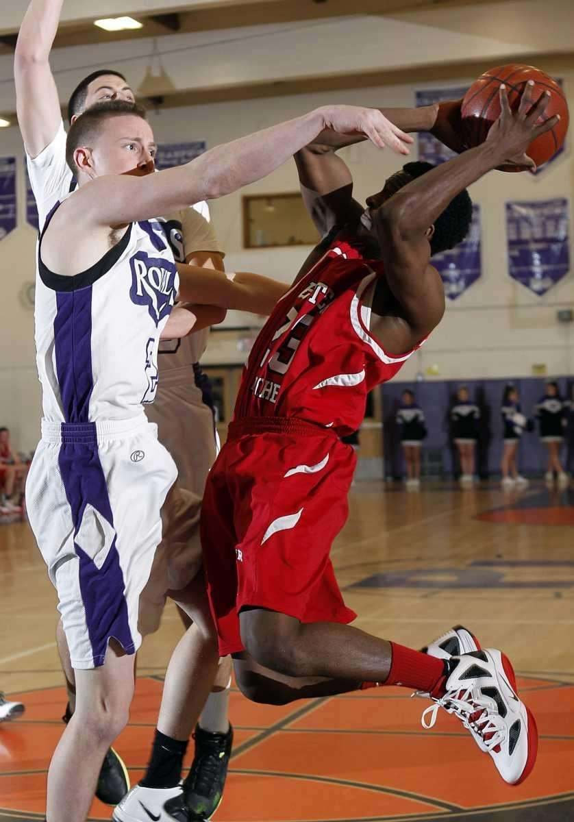 Center Moriches' Maleek Harris (23) is fouled by