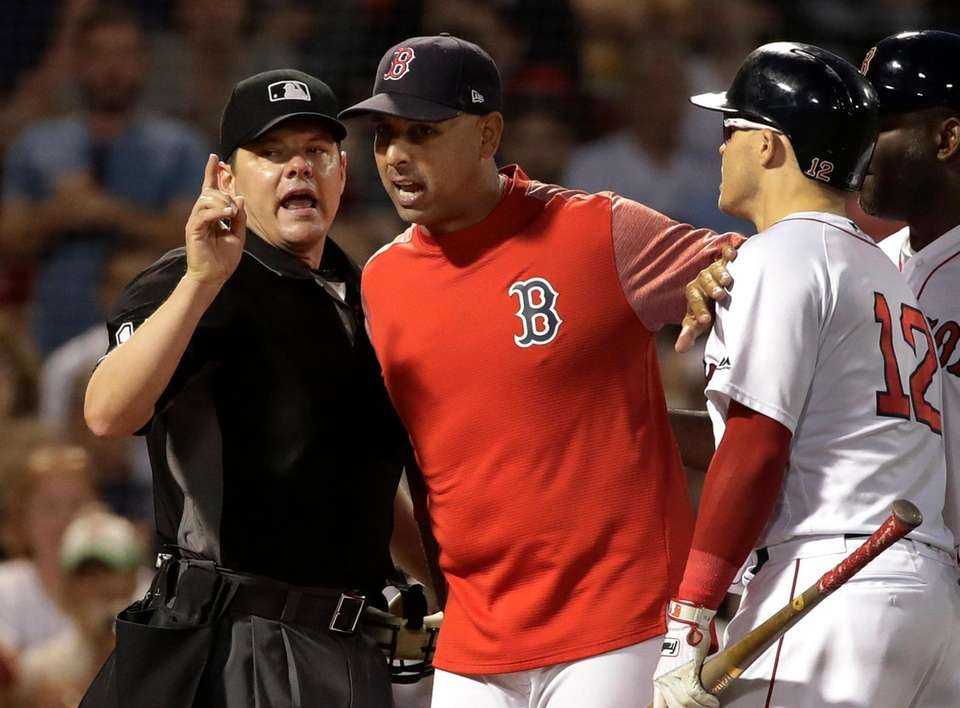 Boston Red Sox manager Alex Cora, middle, keeps