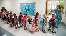 Kindergarten teacher Dana Thomas leads students on the