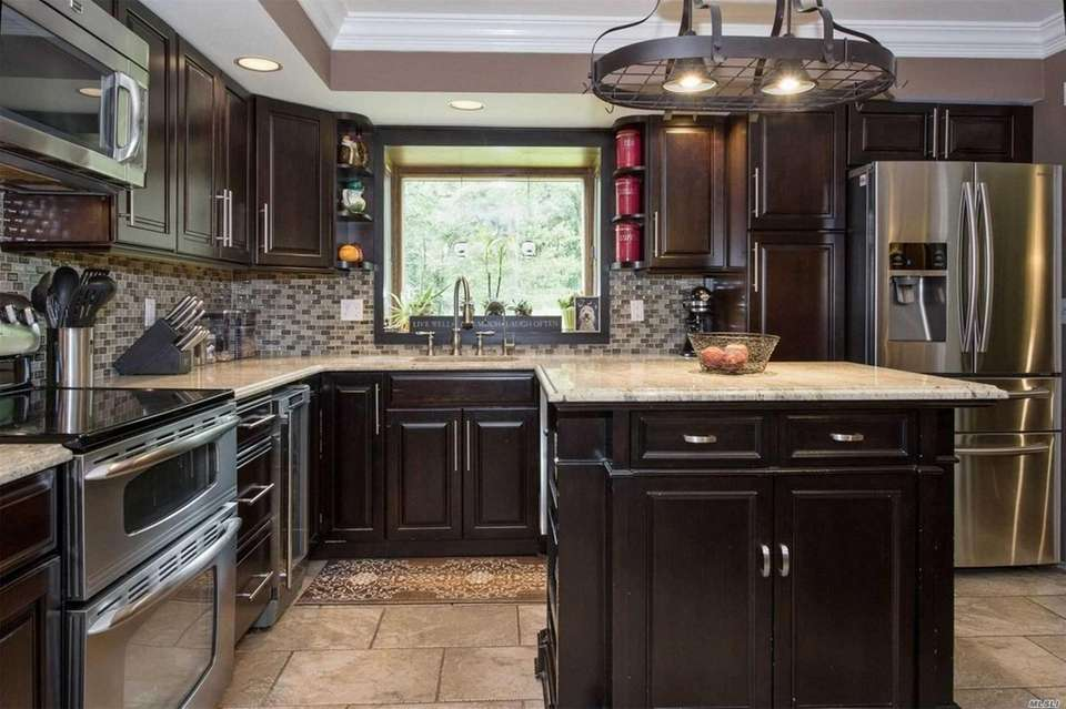 The updated eat-in kitchen includes granite countertops, stainless