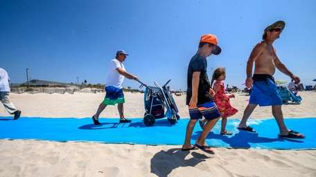 Beachgoers on Friday use new blue mats that