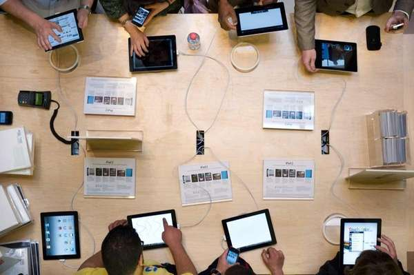 Customers look at iPads 2 displayed on March