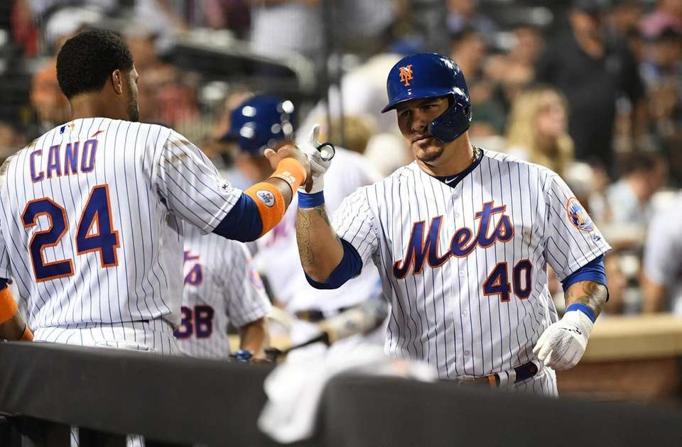 New York Mets catcher Wilson Ramos is greeted