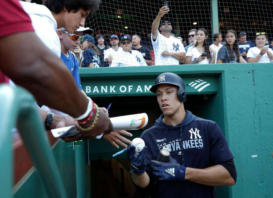 Yankees' Aaron Judge signs autographs before a game