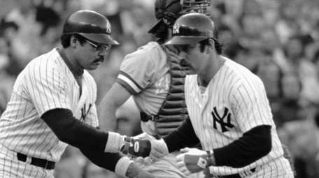 Yankees catcher Thurman Munson, right, is congratulated by