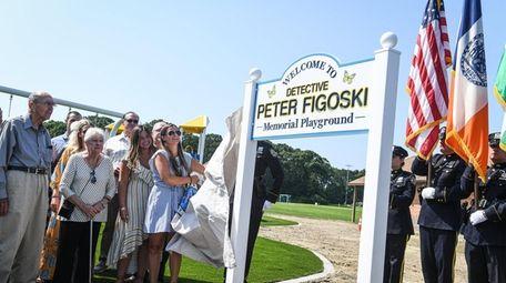 Caroline Figoski unveils the sign for the playground