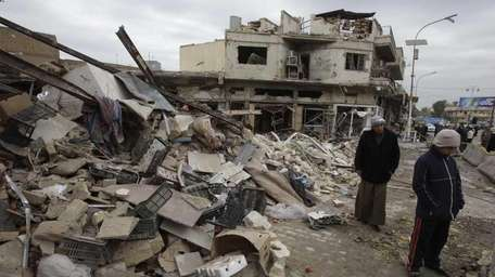People walk past destroyed buildings at the scene